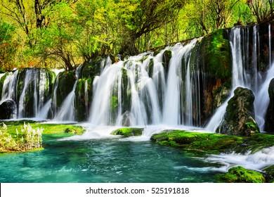 Erstaunlicher Wasserfall und azurblauer See mit kristallklarem Wasser unter grünen Wäldern im Naturschutzgebiet Jiuzhaigou (Jiuzhai Valley National Park) der Provinz Sichuan, China. Schöne Sommerwaldlandschaft