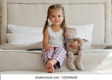 Nettes kleines Mädchen im Pyjama, das ihren Spielzeughasen auf dem Bett zu Hause umarmt, glückliches Kindheitskonzept, horizontales Innenporträt