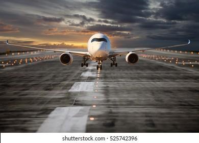 Avión de pasajeros en la pista del aeropuerto. El avión despega a la hora del atardecer. Vista frontal del avión.