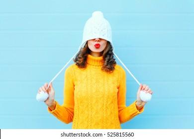 Glückliches kühles Mädchen, das rote Lippen bläst, macht Luftkuss, der eine Strickmütze, gelben Pullover über blauem Hintergrund trägt