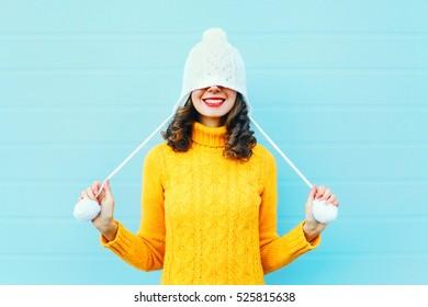 Mode glückliche junge Frau in Strickmütze und Pullover, die Spaß über buntem blauem Hintergrund haben