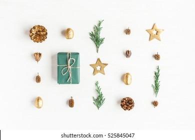 Composición navideña. Regalo, adornos navideños dorados, ramas de ciprés, piñas sobre fondo blanco. Endecha plana, vista superior