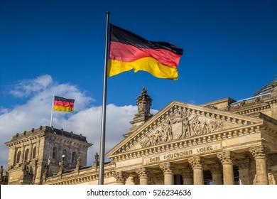 Banderas alemanas ondeando en el viento en el famoso edificio del Reichstag, sede del Parlamento alemán (Deutscher Bundestag), en un día soleado con cielo azul y nubes, distrito central de Berlín Mitte, Alemania