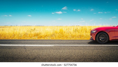 Sport car parked on road side with field of golden wheat background .