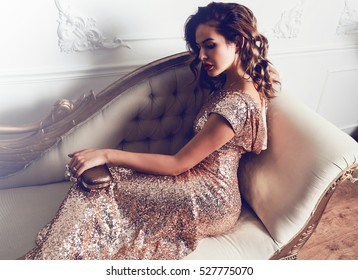 Hermosa jovencita impresionante con un increíble vestido de lentejuelas brillantes sentado en un sillón de lujo, con un bolso de mano moderno. Labios carnosos de color rojo brillante, maquillaje de Hollywood.