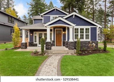 Schönes Äußeres eines neu gebauten Luxushauses. Hof mit grünem Gras und Gehweg führen zu kunstvoll gestalteten überdachten Veranda und Eingang.
