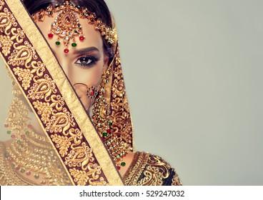 美しいインドの女の子の肖像画。ゴールデンクンダンジュエリーセットの若いヒンドゥー教の女性モデル。伝統的なインドの衣装lehengacholi。