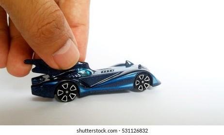 Dedo sosteniendo batmobile azul fundido a presión.
