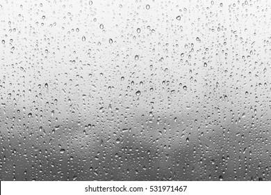 曇りの背景を持つウィンドウガラスの表面に雨粒。曇りの背景に分離された雨滴の自然なパターン。