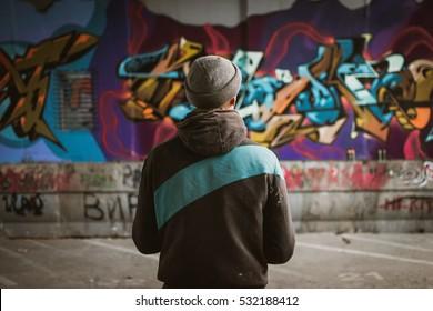 壁の近くに立っているグラフィティアーティスト