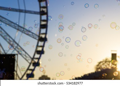 Many floating bubbles with a blurred background of giant wheel against a sunset sky