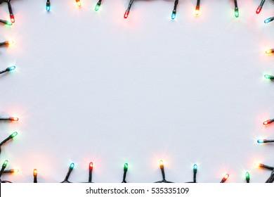 bunte leuchtende Girlande auf weißem Hintergrund Weihnachtsrahmenmodell