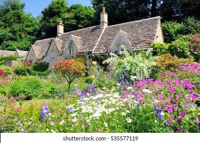 コッツウォルズ、イギリス、イギリスの日差しの中で美しい花の庭とイングリッシュカントリーコテージ