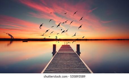Perspektivische Ansicht eines hölzernen Piers auf dem Teich bei Sonnenuntergang mit perfekt spiegelnder Reflexion