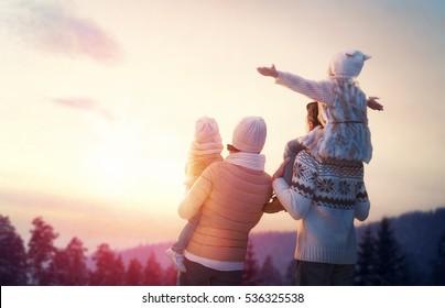 Glückliche Familie bei Sonnenuntergang. Vater, Mutter und zwei Kinder Töchter haben Spaß und spielen auf einem schneebedeckten Winterspaziergang in der Natur. Das Kind sitzt auf den Schultern seines Vaters. Frost Wintersaison.