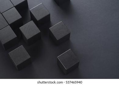Schwarze Holzwürfel auf einem schwarzen Hintergrund, Draufsicht. Abstrakter Hintergrund mit Würfeln mit Kopierraum.