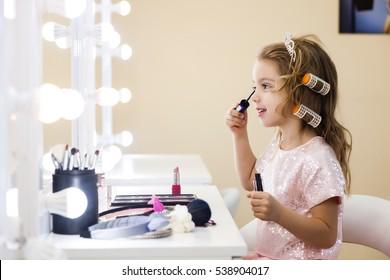 beautiful little girl in the mirror preening. little beauty