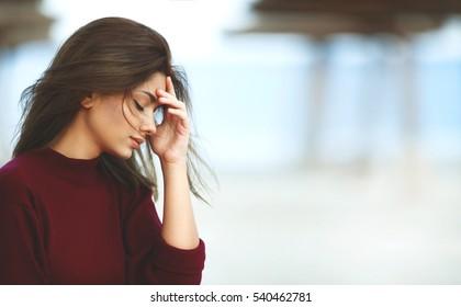 Gestresste Frau mit Kopfschmerzen am Strand. Traurige Frau im Freien