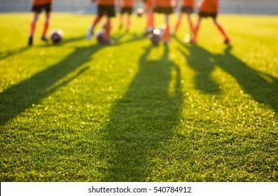 学校のぼやけたサッカー場。ピッチでトレーニングする若いサッカー選手。サッカースタジアムの草の背景