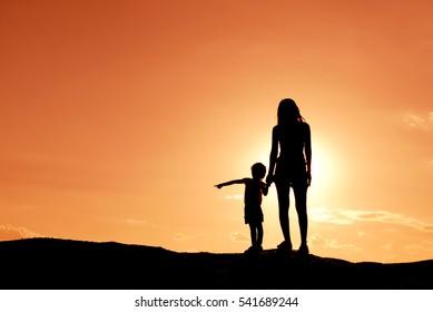 Silhouetmoeder en dochter bij de hemelzonsondergang.