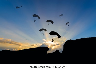 Parachuting exit from a helicopter at sunset.