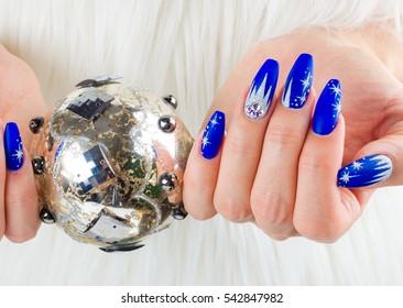 Uñas decoradas con color azul y estrellas brillantes para celebrar la Navidad y la última del año.
