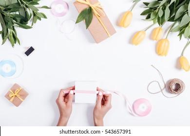 Caja de cinta atada a mano femenina con un regalo en la mesa blanca, vista superior