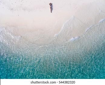 Junge Frau in einem Bikini, der auf dem Rücken auf dem weißen Sand nahe den Wellen des blauen Meeres liegt. Draufsicht. Kai Insel, Andamanensee, Phuket, Thailand. Luftaufnahmen.
