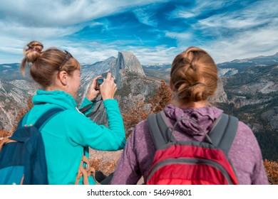 写真を撮り、アメリカのヨセミテ国立公園の景色を楽しむバックパックを持った2人のハイカー
