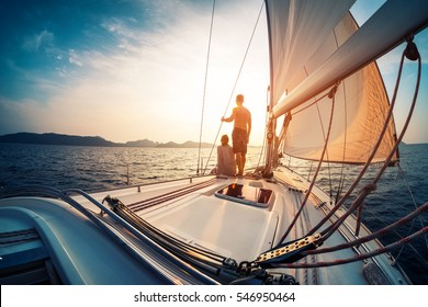Couple enjoying sunset from the deck of the sailing boat moving in a sea