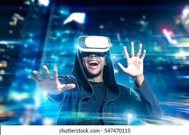 Retrato de un hombre afroamericano emocionado con gafas de realidad virtual jugando en una ciudad de noche. Imagen tonificada. Exposicion doble
