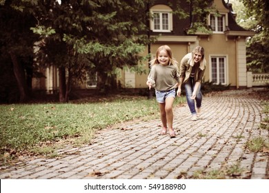Mom and daughter playing in front of house.