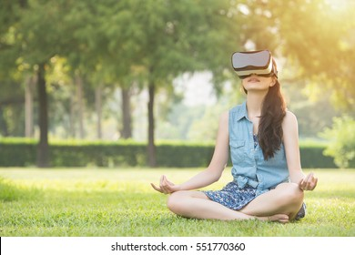 mooie Aziatische vrouw geniet van zen virtual reality zittend op het gras in openluchtpark. VR-headset bril apparaat. natuur buitenshuis achtergrond. mensen en technologie concept