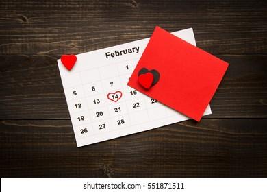 バレンタインデーの背景。バレンタインカードと木製の机の上のカレンダー。