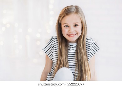 Laughing cute girl portrait at home. Little child smiling and looking at camera
