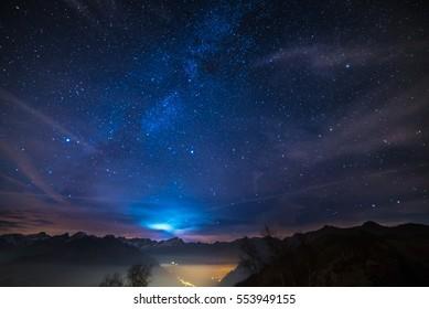 クリスマスの時期の素晴らしい星空とイタリアのフランスアルプスの雄大な高山地帯。下には輝く村があり、雲の後ろには月明かりがあります。
