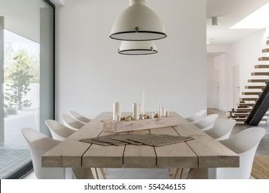 Habitación con mesa de comedor de madera, sillas blancas y lámpara industrial.
