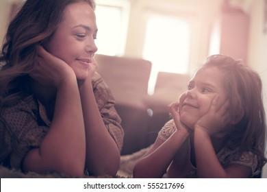 Hermosa rubia caucásica chica tendida en el suelo con su madre y sonriendo.