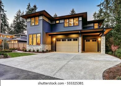 Luxuriöses Neubauhaus in Bellevue, WA. Das moderne Haus verfügt über eine Garage für zwei Autos, die von einem blauen Abstellgleis und einer Wandverkleidung aus Naturstein eingerahmt ist. Nordwesten, USA