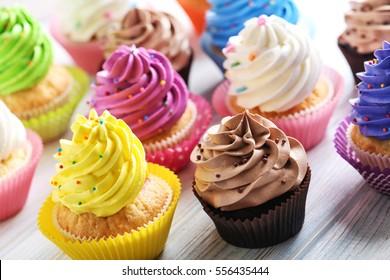 Deliciosos cupcakes en una mesa de madera blanca