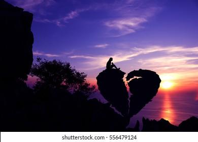 Frauen sitzen auf gebrochenem herzförmigem Stein auf einem Berg mit Sonnenunterganghintergrund des purpurnen Himmels. Silhouette Valentine Hintergrundkonzept.