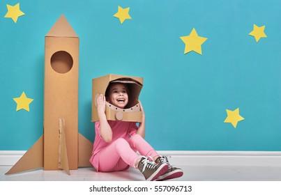 Kind Mädchen in einem Astronautenkostüm mit Spielzeugrakete spielen und träumen davon, ein Raumfahrer zu werden. Porträt des lustigen Kindes auf einem Hintergrund der hellen blauen Wand mit gelben Sternen.