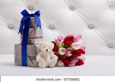 テディベアはチューリップとギフトボックスの花束の近くに新聞テクスチャとブルーのリボンで座っています。おもちゃと花のクローズアップ。はがきの背景。母の日おめでとう。