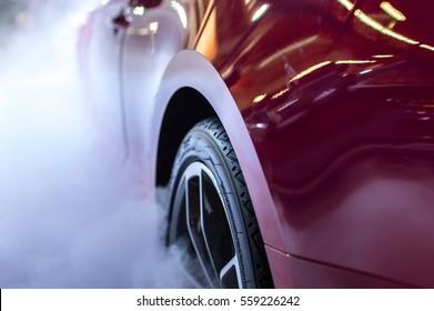 Red car wheel in fog or smoke