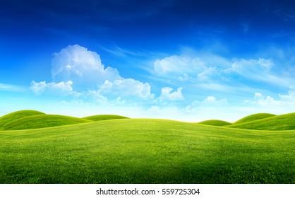 Grünes Grasfeld auf kleinen Hügeln und blauem Himmel mit Wolken