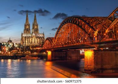 Escena al atardecer en Colonia (Koln) en la región de Renania del Norte Westfalia de Alemania, sorprendiendo a la Catedral de Colonia (Kolner Dom) y el Puente Hohenzaller sobre el río Rin.