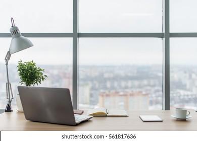Lugar de trabajo con computadora portátil Cómoda mesa de trabajo en ventanas de oficina y vista a la ciudad.