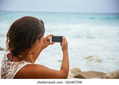 Schöne Frau, die ein Foto eines Ozeans am Strand macht.