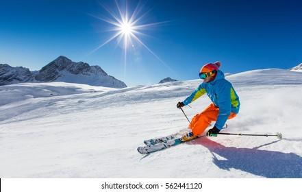 Skifahrer Skifahren bergab an einem sonnigen Tag im Hochgebirge