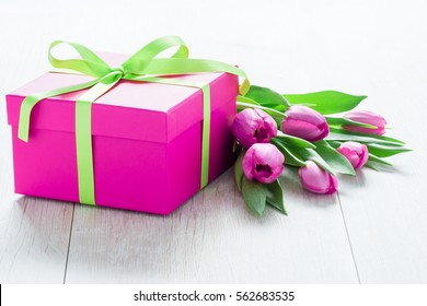 Pink Tulip Flowers and Pink Gift box on rustic table for March 8, International Womens Day, Birthday , Valentines Day or Mothers day